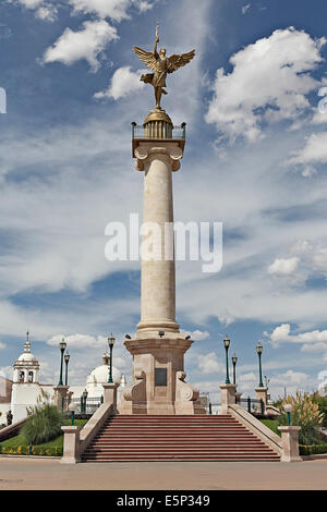 The Angel of Liberty statue, monument, in the Plaza in downtown Chihuahua City, Chihuahua Mexico with old church - Stock Image