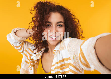 Image of a cute beautiful young curly girl posing isolated over yellow wall background take selfie by camera. - Stock Image