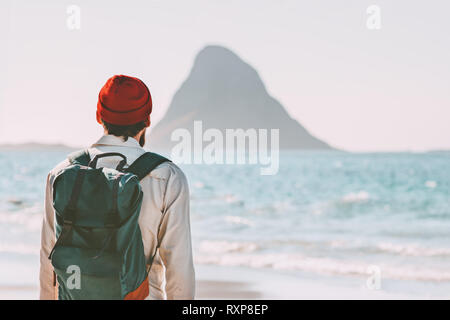 Traveler man enjoying Bleiksoya view walking alone on beach ocean travel with backpack active lifestyle adventure summer vacations in Norway trip outd - Stock Image