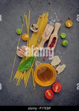 Italian food concept. Spaghetti with ingredients sweet basil ,tomato ,garlic peppercorn ,champignon,zucchini and parmesan cheese on dark background fl - Stock Image