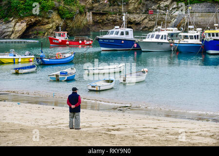 A mature man standing on the shore in Newquay Harbour in Cornwall. - Stock Image