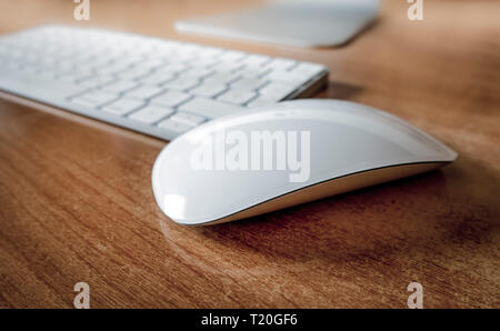 White wireless mouse on office desk with keyboard behind. - Stock Image