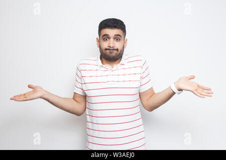 I don't know. Portrait of confused handsome bearded young man in striped t-shirt standing with raised arms and dont know what to do. indoor studio sho - Stock Image