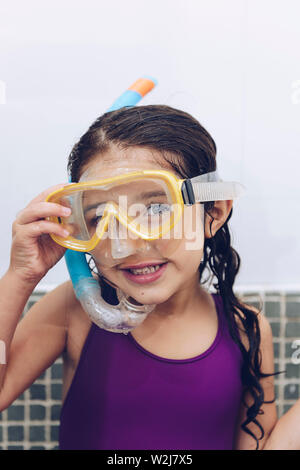 vertical portrait of a happy pretty little girl smiling with snorkel goggles in the tub while taking a bath in the bathtub, kids hygiene concept, copy - Stock Image