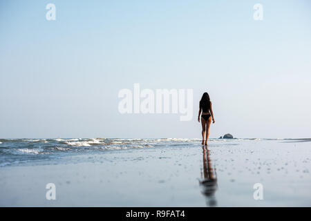 Slim beautiful lady walks at lonely sea beach. Space for text - Stock Image