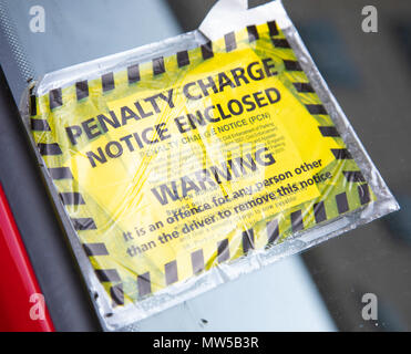 A yellow and black parking penaty charge notice attached to a parked car Liverpool May 2018 - Stock Image