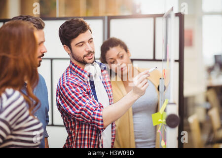 Executive explaining strategy from whiteboard at creative office - Stock Image