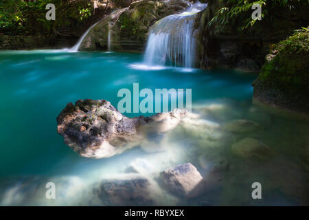 Turquoise-colored water of the Kawasan waterfalls located on Cebu Island, Philippines - Stock Image
