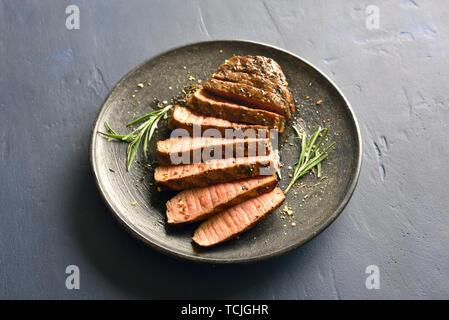 Medium rare roast beef on plate over stone background - Stock Image