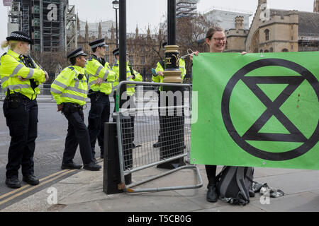 Police officers seal off Parliament Square during the week-long protest by climate change activists with Extinction Rebellion's campaign to block road junctions and bridges around the capital, on 23rd April 2019, in London England. - Stock Image