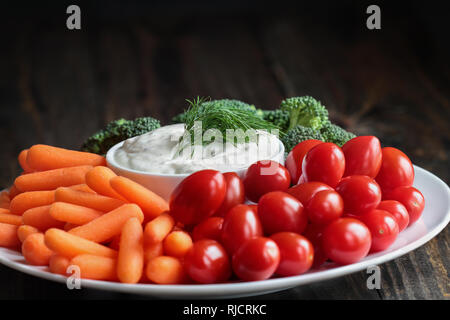 Homemade buttermilk ranch salad dressing with dill served with fresh vegetables, cherry tomatoes, baby carrots and broccoli, over a rustic wooden back - Stock Image