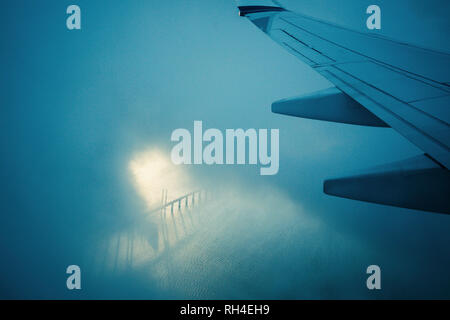 Airplane wing flying through clouds over water - Stock Image