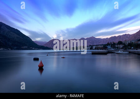 Sunset in bay of Kotor Montenegro.   Water appears flat, and wispy cloud effect, in a bay surrounded by jagged glowing mountain. - Stock Image
