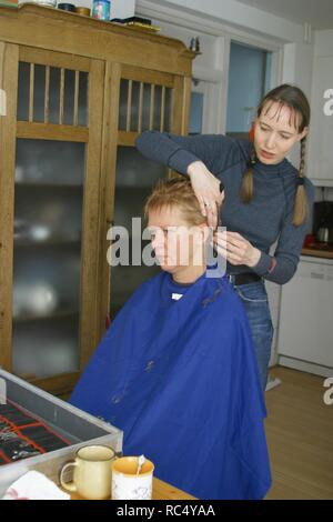 Home hairdresser cutting hair from friend at home - Stock Image
