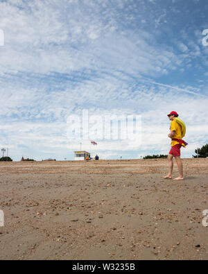 A lifeguard stood on a British pebble beach in summer - Stock Image