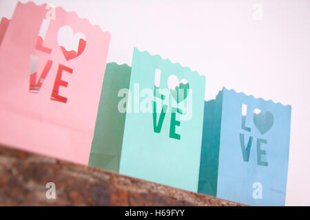 Tealight candle bags love heart colorful wood shelf wall wooden board on a white white pink pink petrol green light - Stock Image