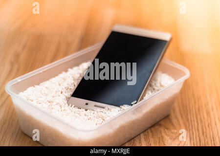 Water damaged phone drying in rice - Stock Image