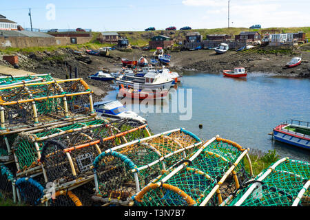 Fishing boats aground at low tide in Paddys Hole Harbour, on a spring day with traditional lobster or crab pots in the foreground at Teesmouth Redcar - Stock Image