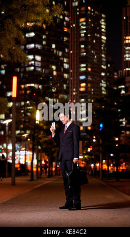 Smiling businessman with smartphone standing against night view of city - Stock Image