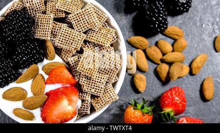 Healthy Breakfast Cereals With Fresh Fruit , Shreddies, or Shredded Wheat,Strawberries, Blackberries, Almonds and Yogurt. - Stock Image
