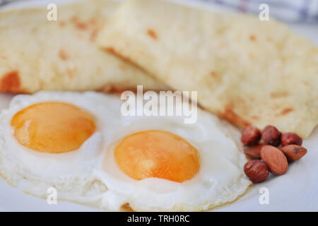 Egg omelet with tortilla bread in a plate as healthy breakfast - Stock Image