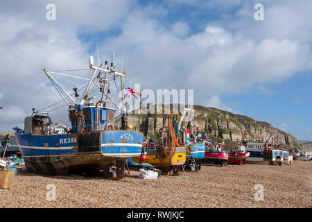 Hastings, East Sussex, UK. 7th March 2019. Fishing boats pulled up high on the Old Town Stade Fishermen's beach out of reach of the sea in the strong blustery windy conditions. With more than 25 boats Hastings has the largest beach-launched fishing fleet in Europe. - Stock Image