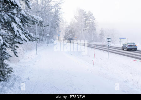 Bike path next to car road in winter time. - Stock Image