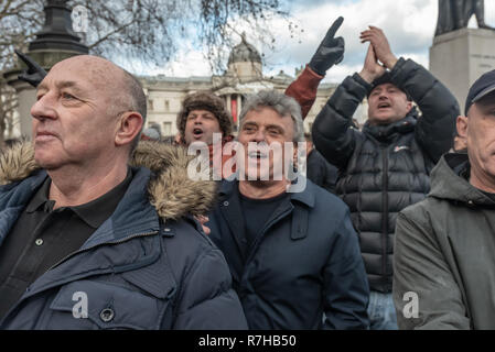London, UK. 9th Dec, 2018. A small group of men shout insults at the marchers as the go thorugh Trafalgar Square. Police have to hold back antifascists who want to challenge them. I was threatened with violence for photographing them The united counter demonstration by anti-fascists was in opposition to Tommy Robinson's fascist pro-Brexit march. Police had issued conditions on both events designed to keep the two groups well apart. Credit: Peter Marshall/Alamy Live News - Stock Image