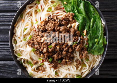 Dan Dan Noodles - Savory and spicy Sichuan noodles served with ground meat closeup on the plate on the table. horizontal top view from above - Stock Image