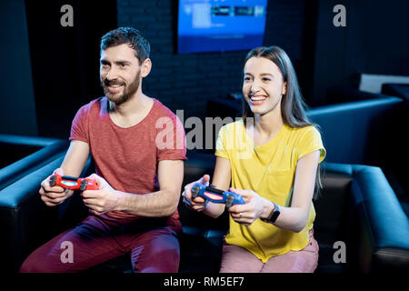Young couple playing video games with gaming console sitting together on the couch in the dark room - Stock Image