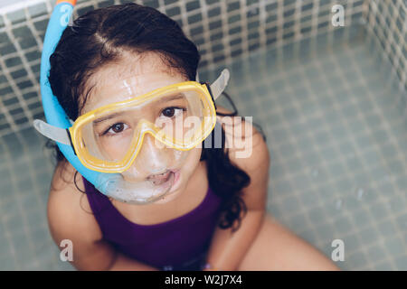 portrait of a pretty little girl having fun with snorkel goggles sitting in the tub while taking a bath in the bathtub, kids hygiene concept, copy spa - Stock Image