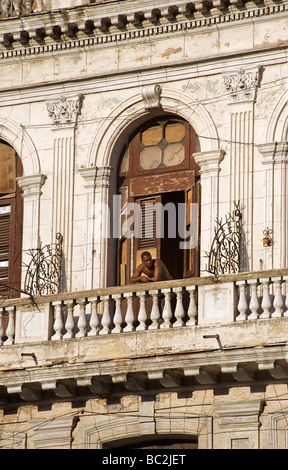 Man at the balcony of his room. Facade of a colonial building, now in multi occupancy. Central Plaza, Havana. Cuba - Stock Image