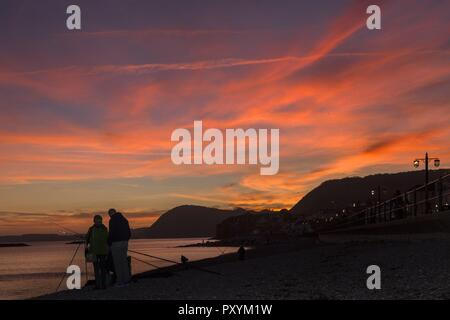 Sidmouth, 24th Oct 18 People cast fishing on the shoreat Sidmouthexperience a spectacular sunset. Photo Central/Alamy Live News - Stock Image