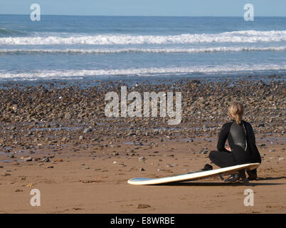 Surfer crouched on the beach watching the waves, Widemouth Bay, Bude, Cornwall, UK - Stock Image
