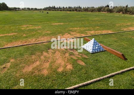 Golf driving range with pyramid of balls tee divots and ready to practice - Stock Image