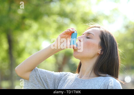 Woman is using an asthma inhaler outdoors in a green park - Stock Image