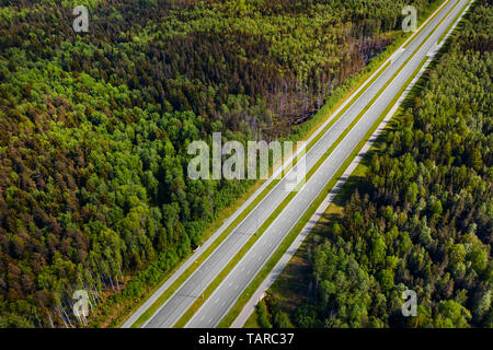 Straight empty highway through deep forest aerial view. Bright summer image at sunny day - Stock Image