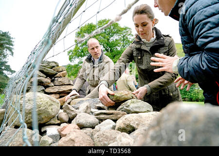 The Duke and Duchess of Cambridge take part in the repair of a dry stone wall at Deepdale Hall Farm, a traditional fell sheep farm, in Patterdale, during a visit to Cumbria. - Stock Image