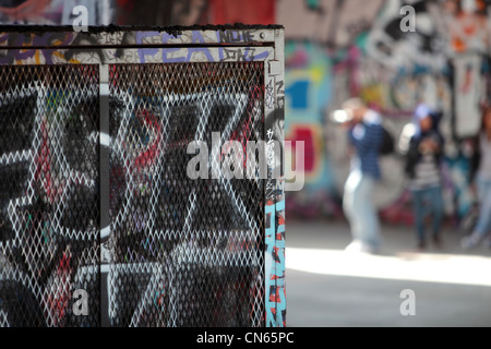 Young adults taking photos in London skatepark with graffiti - Stock Image