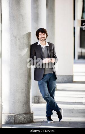 Young man laughingly leans against column with smartphone in hand, North Rhine-Westphalia, Germany - Stock Image
