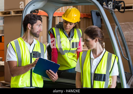 Warehouse workers talking with forklift driver - Stock Image