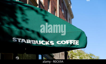 A Starbucks coffee shop outdoor umbrella clearly showing the Stabucks brand name and brand colours on a bright sunny day - Stock Image