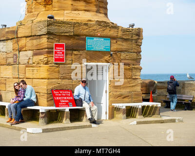 The keeper at the West lighthouse at Whitby harbour UK, open for visitors on a bright spring day - Stock Image