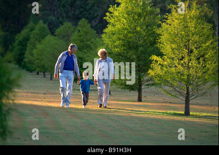 Grandparents walking with grandson - Stock Image
