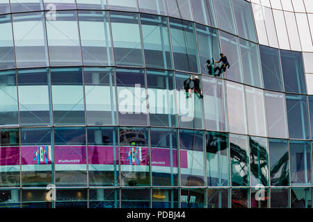Two window cleaners working on the Sage, a landmark concert hall in a curved glass and stainless steel building which opened in 2004, Gateshead, UK. - Stock Image