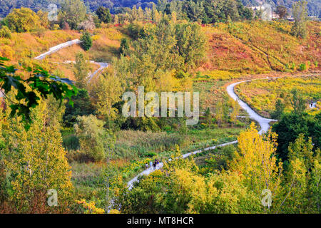 People walking on scenic hiking trail in Evergreen Brickworks in autumn - Stock Image