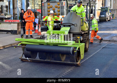 Road resurfacing with this machine laying down a mesh reinforcement on top of 1st tarmac layer with 2 more layers to finish - Stock Image
