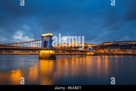 Budapest, Hungary - Beautiful Szechenyi Chain Bridge in unique blue colour with Buda Castle Royal Palace at background at dusk - Stock Image
