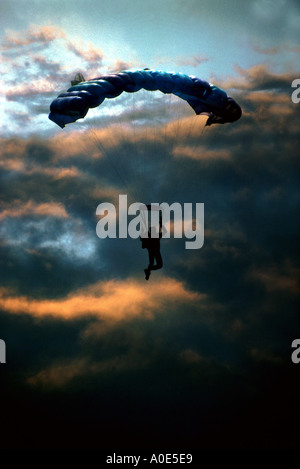 Sunset Descent. A Paraglider in Silhouette Against a Colorful Evening Sky - Stock Image