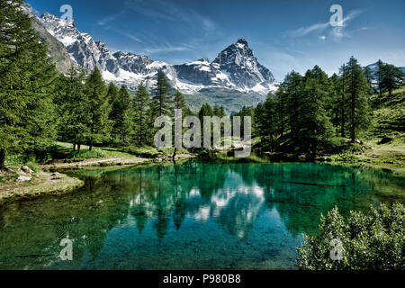 The blue lake and the Matterhorn in a scenic summer landscape with sunny lights seen from Breuil-Cervinia, Aosta Valley - Italy - Stock Image